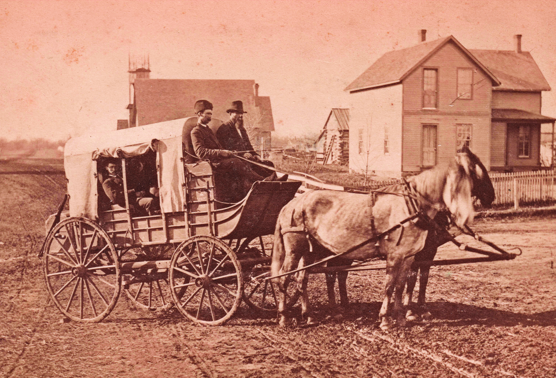 historic photo showing a stagecoach pulled by two horses. two drivers sit at the front, and a man peeks out from behind the canvas covering
